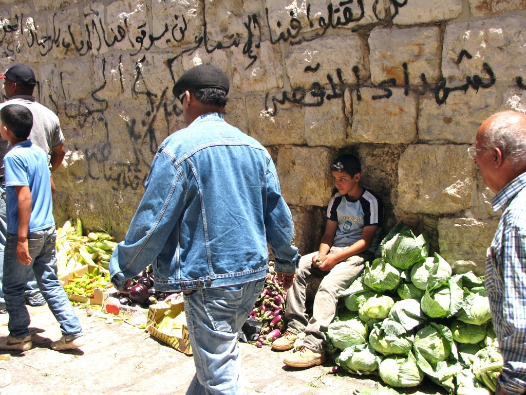 A boy sitting while people pass by in a vegetable market in Bethlehem, in the occupied Palestinian Territories.